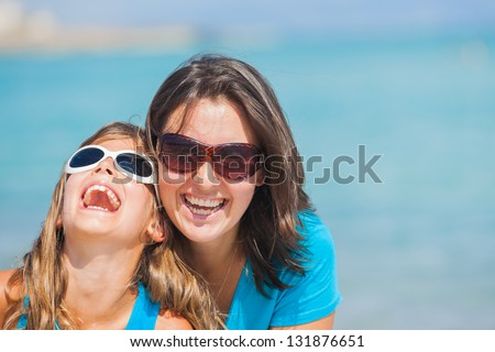 Portrait of mother and her daughter in sunglasses having fun on tropical beach - stock photo