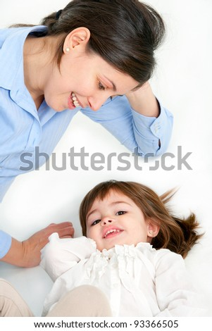 Portrait of mother and her daughter laying on floor. Isolated on white background.