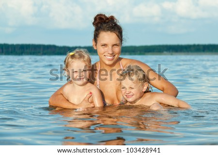 Portrait of mother and her daughters having fun on beach
