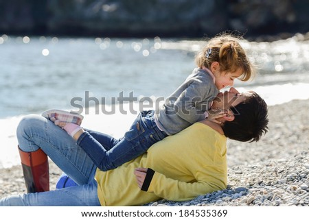 Portrait of mother and her little daughter having fun on the beach