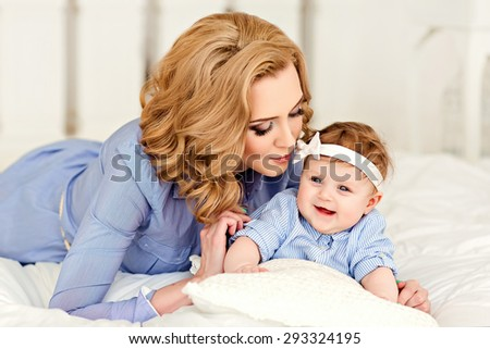 Portrait of mother and little baby girls with blue eyes in a striped blue dress lying on the bed. Mom gently kisses her daughter on the cheek