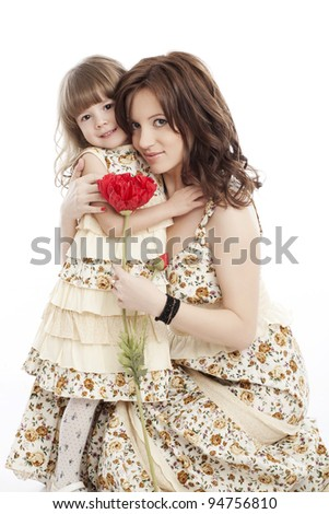 Portrait of mother and little daughter in his arms with a flower - stock photo