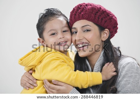 Portrait of mother and son embracing - stock photo