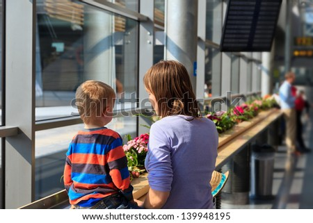 portrait of mother and son in the airport - stock photo