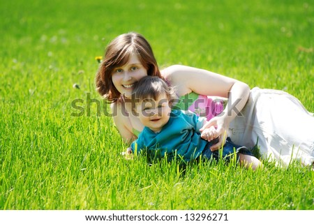 portrait of mother and son on the grass - stock photo