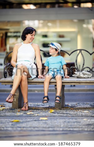 Portrait of mother and son sitting outdoors on beautiful summer day - stock photo