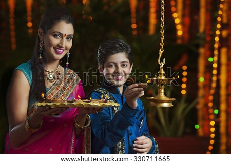 Portrait of mother and son with diyas - stock photo