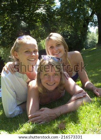 Portrait of mother and teenage daughters laying in grass - stock photo
