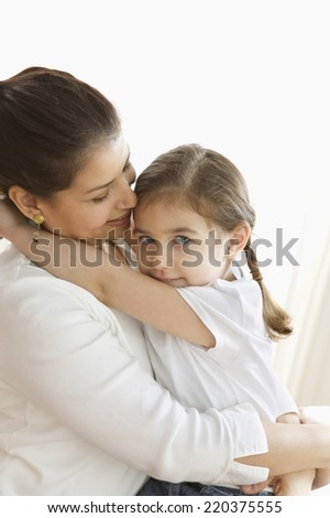 Portrait of mother and young daughter hugging