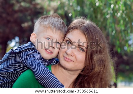 Portrait of mother and young son on summer  day. Family walk in the park - stock photo