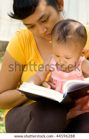 portrait of mother babysitting curious baby girl during readings outdoor - stock photo