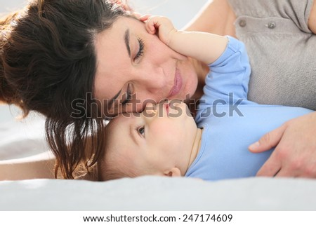 Portrait of mother cuddling baby boy - stock photo
