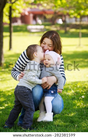 Portrait of mother, daughter and son, happy family of three people, sitting on the meadow in the park outside on a spring summer bright day, hugging, kissing and playing, mothers day concept holiday