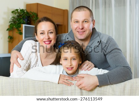 Portrait of mother, father and cute girl together indoors