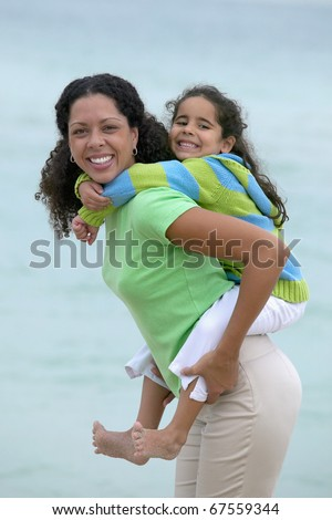 Portrait of mother giving daughter piggy back ride - stock photo