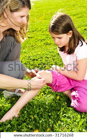 Portrait of mother giving first aid to daughters cut knee - stock photo