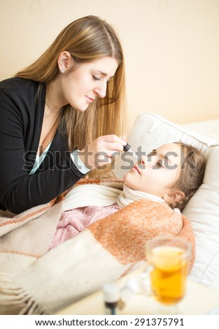 Portrait of mother giving nasal medicines to sick daughter lying in bed - stock photo