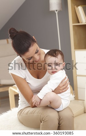 Portrait of mother holding baby boy on lap. Baby looking at camera. - stock photo