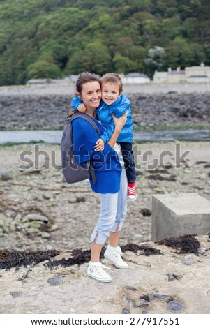 Portrait of mother, holding her child, on the beach, smiling at camera, daytime - stock photo