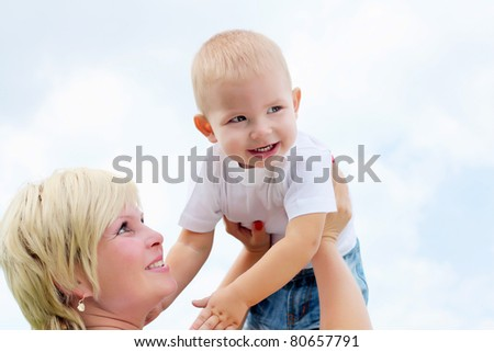 Portrait of mother holding her little baby outdoors in the summer