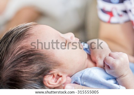 Portrait of mother holding her newborn baby