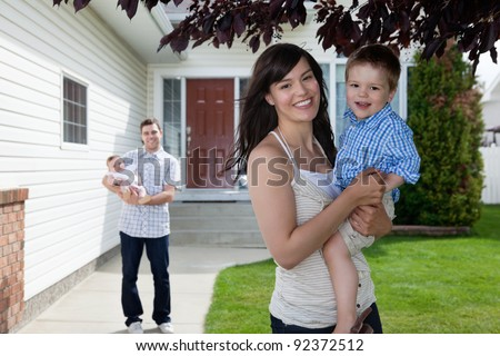 Portrait of mother holding her son while father standing behind holding baby