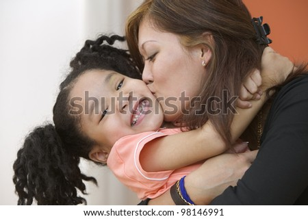 Portrait of mother hugging and kissing young daughter - stock photo
