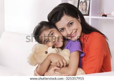 Portrait of mother hugging daughter with stuffed toy - stock photo