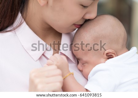 Portrait of mother kissing her adorable child