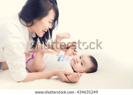 portrait of mother lie on white with her baby boy. - stock photo