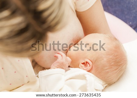 portrait of mother nursing her baby - stock photo