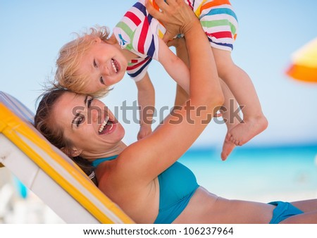Portrait of mother playing with baby on beach