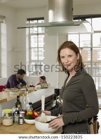 Portrait of mother preparing salad with family sitting in background at home - stock photo