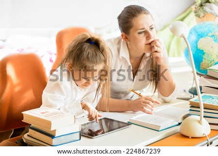 Portrait of mother sitting next to daughter doing homework - stock photo