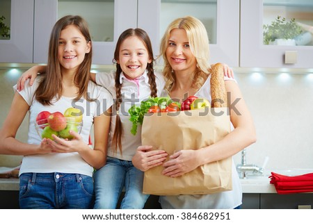 Portrait of mother standing near her daughters with paper bag