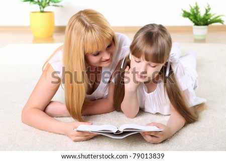 portrait of mother together with daughter with book in studio