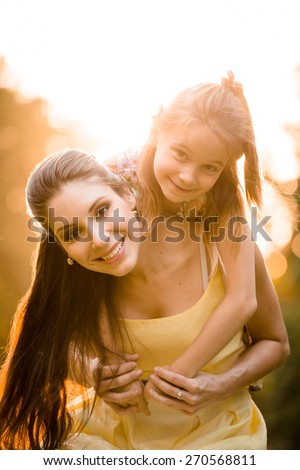 Portrait of mother with child enjoying together in sunny nature - stock photo