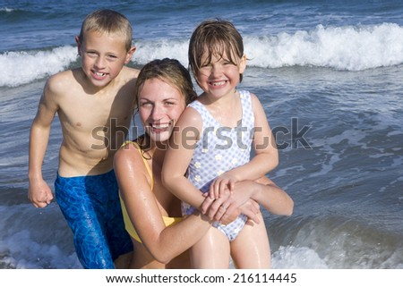 Portrait of mother with children in sea - stock photo