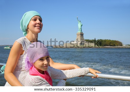 Portrait of mother with daughter on a boat in front of the famous Statue of Liberty in New York - stock photo