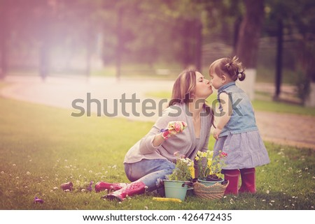 Portrait of mother with daughter planting flowers into the flowerpot in the garden