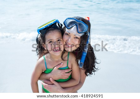 Portrait of mother with daughter wearing diving goggles at beach - stock photo