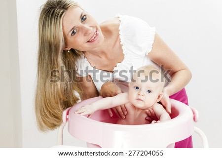 portrait of mother with her baby during bathing - stock photo