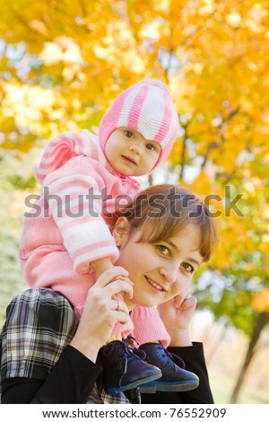Portrait of mother with her baby in autumn park - stock photo