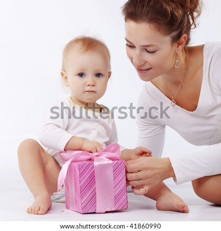 Portrait of mother with her baby opening gift box in white studio - stock photo