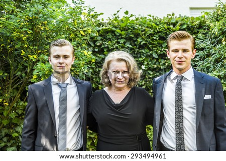 portrait of mother with her two adolescent sons, dressed in suit with tie - stock photo