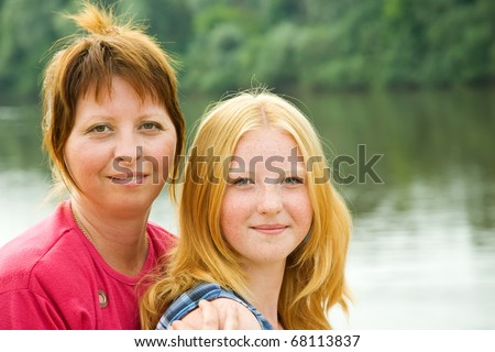 Portrait of mother with teenager daughter against landscape - stock photo