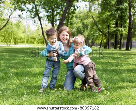 Portrait of mother with two children summer outdoors