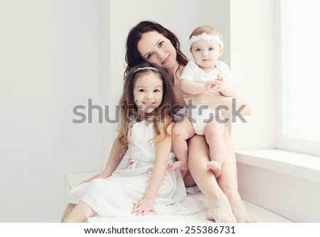 Portrait of mother with two daughters in white room near window - stock photo