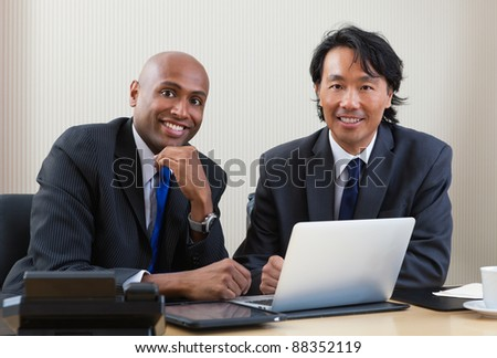 Portrait of multi ethnic business people working on laptop and digital tablet - stock photo