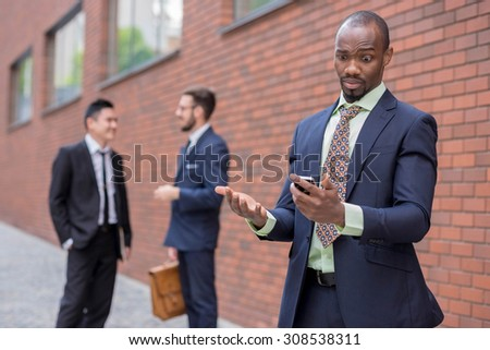Portrait of multi ethnic business team. Three happy smiling men standing against the backdrop of the city. The African-American man  talking on the phone , other is Chinese and European. concept of - stock photo